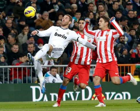 Real Madrid's Sergio Ramos does a scissors kick in front of Atletico Madrid's Koke and Diego Costa during their Spanish first division soccer match at Santiago Bernabeu stadium in Madrid