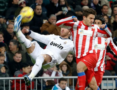 Real Madrid's Sergio Ramos does a scissors kick in front of Atletico Madrid's Koke during their Spanish first division soccer match at Santiago Bernabeu stadium in Madrid