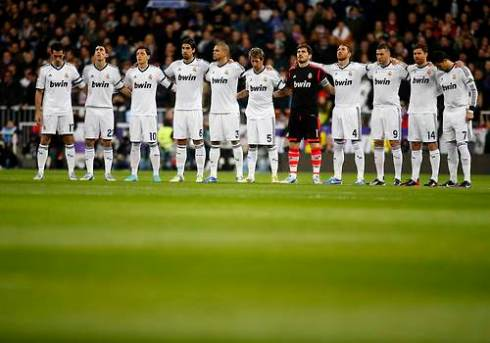 Real Madrid players observe a minute of silence, in memory of the fifth victim who died trampled in a concert last month, before their Spanish first division match against Atletico Madrid in Madrid