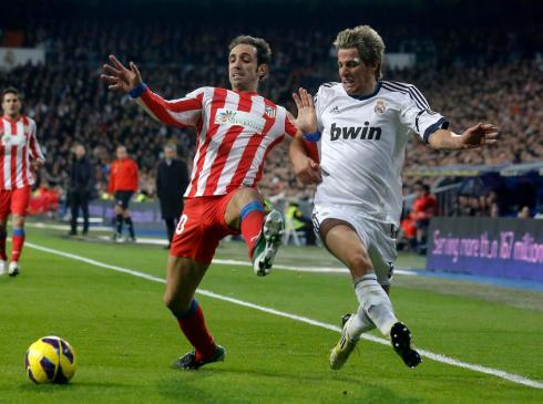 Real Madrid's Fabio Coentrao fights for the ball with Atletico Madrid's Juanfran during their Spanish first division soccer match at Santiago Bernabeu stadium in Madrid
