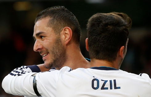 Real Madrid's Mesut Ozil celebrates a goal with teammate Karim Benzema during their Spanish First Division soccer match against Real Betis at Santiago Bernabeu stadium in Madrid