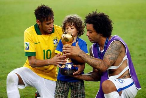 Brazil's Marcelo helps his son hold the trophy as teammate Neymar looks on as they celebrate winning their Confederations Cup final soccer match against Spain at the Estadio Maracana in Rio de Janeiro