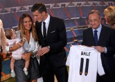 Gareth Bale of Wales talks with his girlfriend Emma and daughter Alba as Real Madrid's president Perez holds his nw jersey at the Santiago Bernabeu stadium in Madrid