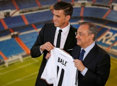 Gareth Bale of Wales hold his new Real Madrid soccer club jersey accompanied by president Florentino Perez at the Santiago Bernabeu stadium in Madrid,
