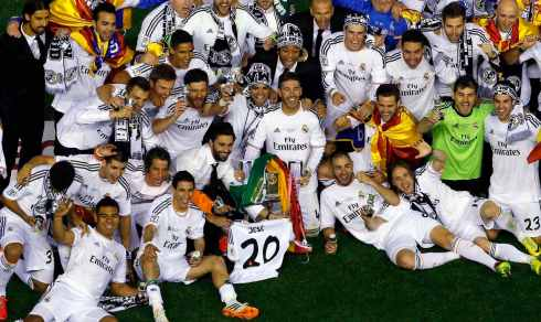 Real Madrid players celebrate with the trophy after winning the King's Cup final soccer match against Barcelona at Mestalla stadium in Valencia