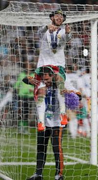Real Madrid's Ramos sits on shoulders as he cuts the net of a goal after defeating Atletico Madrid in the their Champions League final soccer match at the Luz Stadium in Lisbon