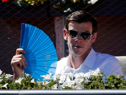 Real Madrid's soccer player Bale cools off with a fan as he watches the match between Nadal of Spain and Berdych of the Czech Republic at the Madrid Open tennis tournament