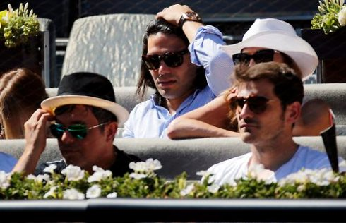 Monaco's soccer player Falcao of Colombia adjusts his hair next to Real Madrid's captain Casillas and Spanish singer Sanz as they watch the match between Nadal of Spain and Berdych of the Czech Republic at the Madrid Open tennis tournament