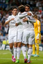 Real Madrid's Cristiano Ronaldo celebrates a goal with his teammates Gareth Bale and James Rodriguez during their Champions League soccer match against FC Basel at Santiago Bernabeu stadium in Madrid