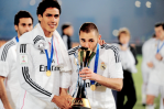 Baby gives a grin while Karim kisses the trophy
