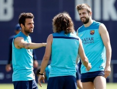 (From L to R) Barcelona's players Cesc Fabregas, Carles Puyol and Gerard Pique speak during a training session at Joan Gamper training camp, near Barcelona May 16, 2014. La Liga is set for one of its most thrilling finishes when Barcelona host leaders Atletico Madrid in a winner-takes-all showdown at the Nou Camp on the final day of the campaign on Saturday. REUTERS/Albert Gea (SPAIN - Tags: SPORT SOCCER)