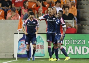 May 18, 2013; Houston, TX, USA; New England Revolution forward Diego Fagundez (14) is congratulated by teammates after scoring a goal during the second half against the Houston Dynamo at BBVA Compass Stadium. Mandatory Credit: Troy Taormina-USA TODAY Sports