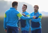 ST ALBANS, ENGLAND - SEPTEMBER 30: Mesut Oezil (C) shares a joke with Mathieu Flamini (R) and Laurent Koscielny (L) during an Arsenal training session ahead of their UEFA Champions League Group D match against Galatasaray at London Colney on September 30, 2014 in St Albans, England. (Photo by Paul Gilham/Getty Images)