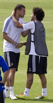 Real Madrid's Pepe from Portugal, left grabs his team mate Marcelo of Brazil around the throat during a training session in Madrid Monday April 4, 2011. Real Madrid will play Tottenham Hotspur Tuesday in a quarter final, 1st leg Champions League soccer match. (AP Photo/Paul White)