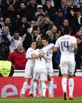 Real Madrid's Portuguese forward Cristiano Ronaldo celebrates with teammates after scoring during the UEFA Champions League round of 16, second leg football match Real Madrid FC vs AS Roma at the Santiago Bernabeu stadium in Madrid on March 8, 2016. / AFP / JAVIER SORIANO (Photo credit should read JAVIER SORIANO/AFP/Getty Images)